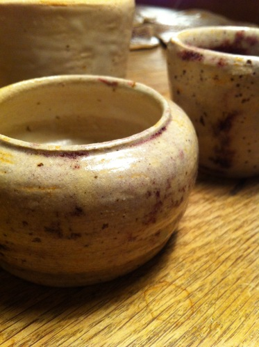 cups in different sizes of white stoneware with purple, yellow glaze